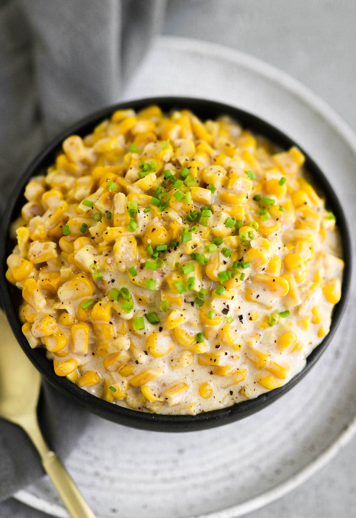 photo of creamed corn in a black bowl with chives on top