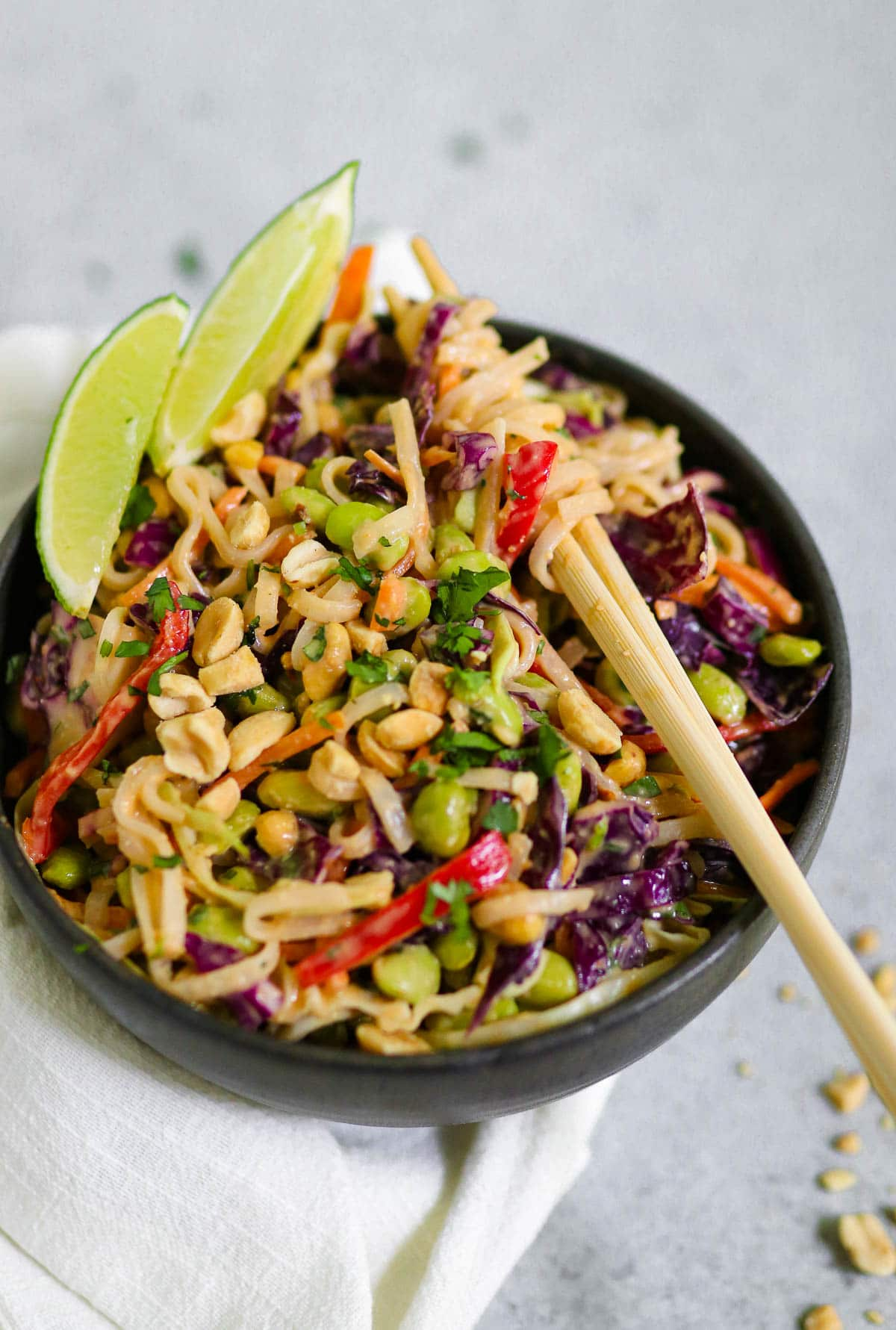 Photo of peanut noodle salad with chopsticks in the noodles in a black bowl