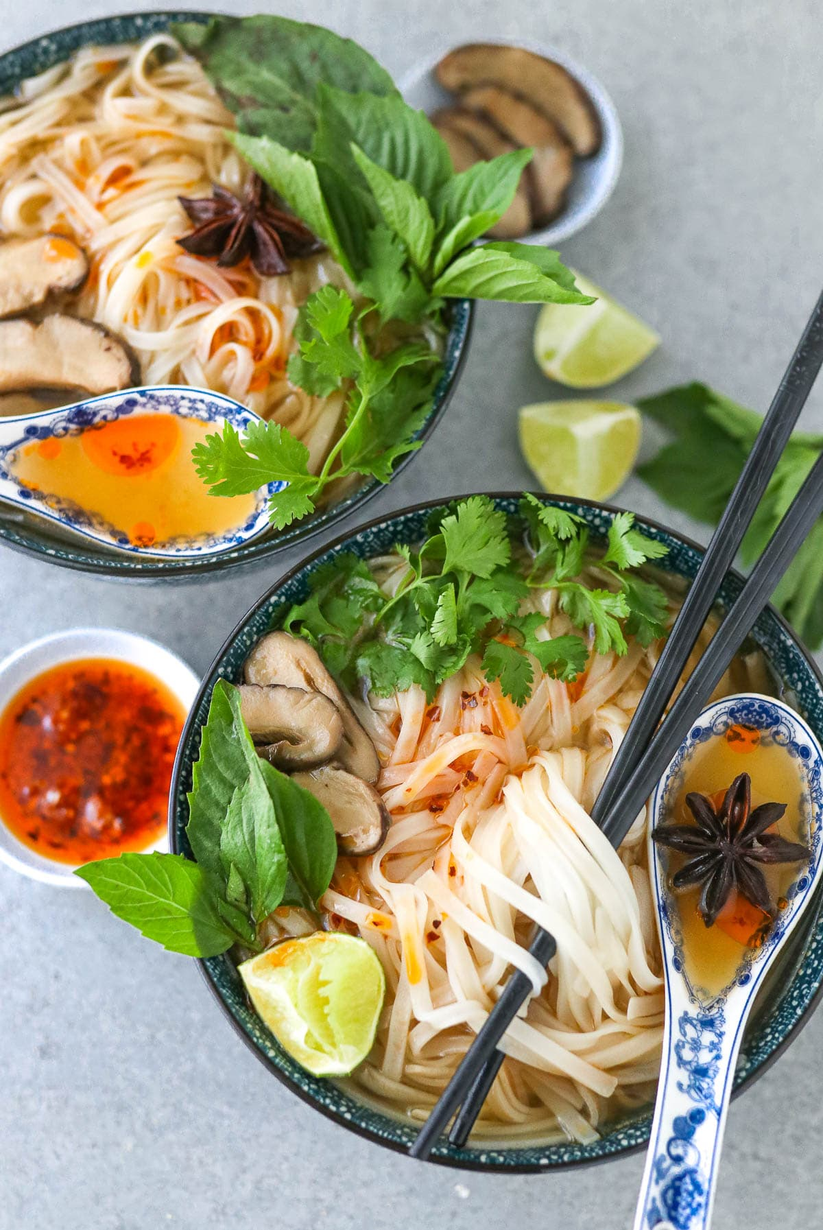 instant pot vegan pho in two bowls with garnishes.