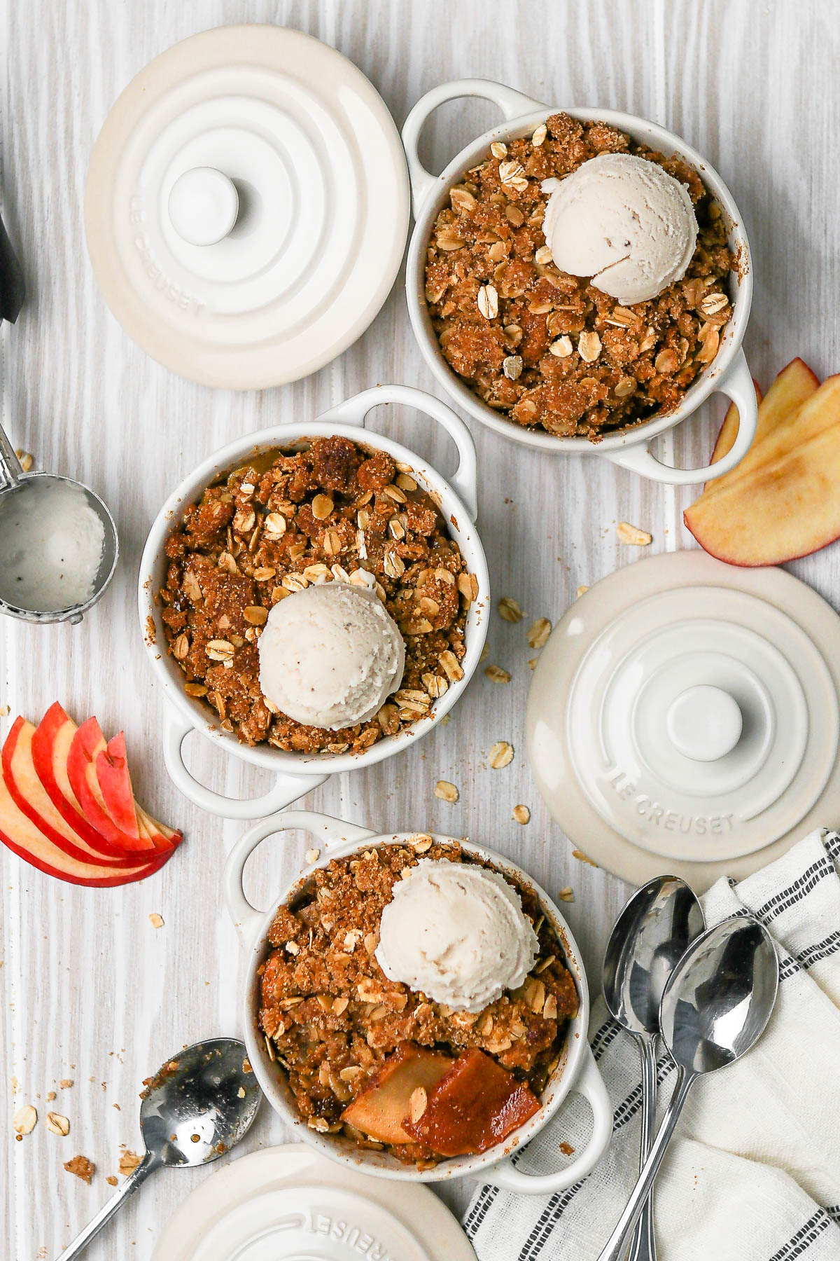 three apple pies in mini pots with garnishes around.