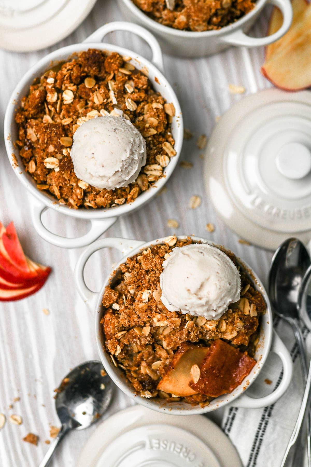 Two baked apple crisp ramekins with ice cream scoop on top.