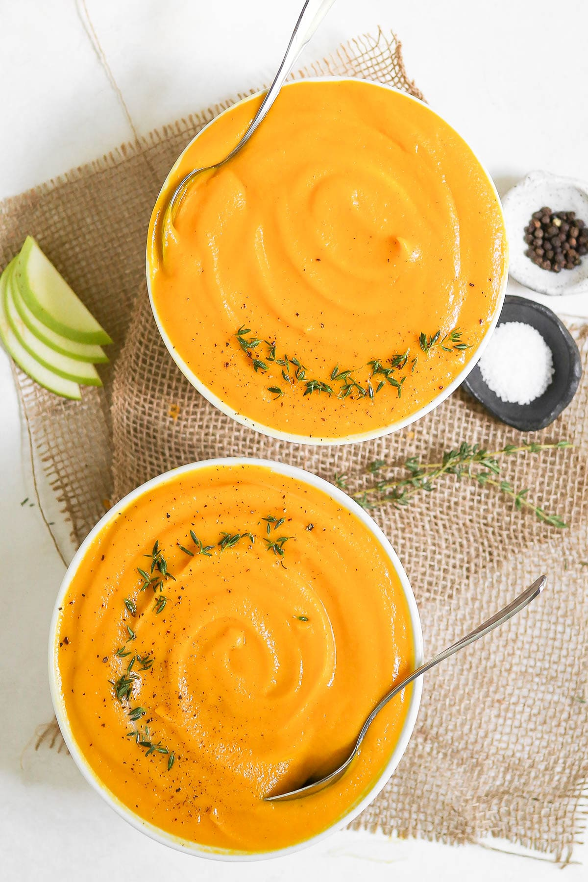 butternut squash soup in two bowls with spoons in them.