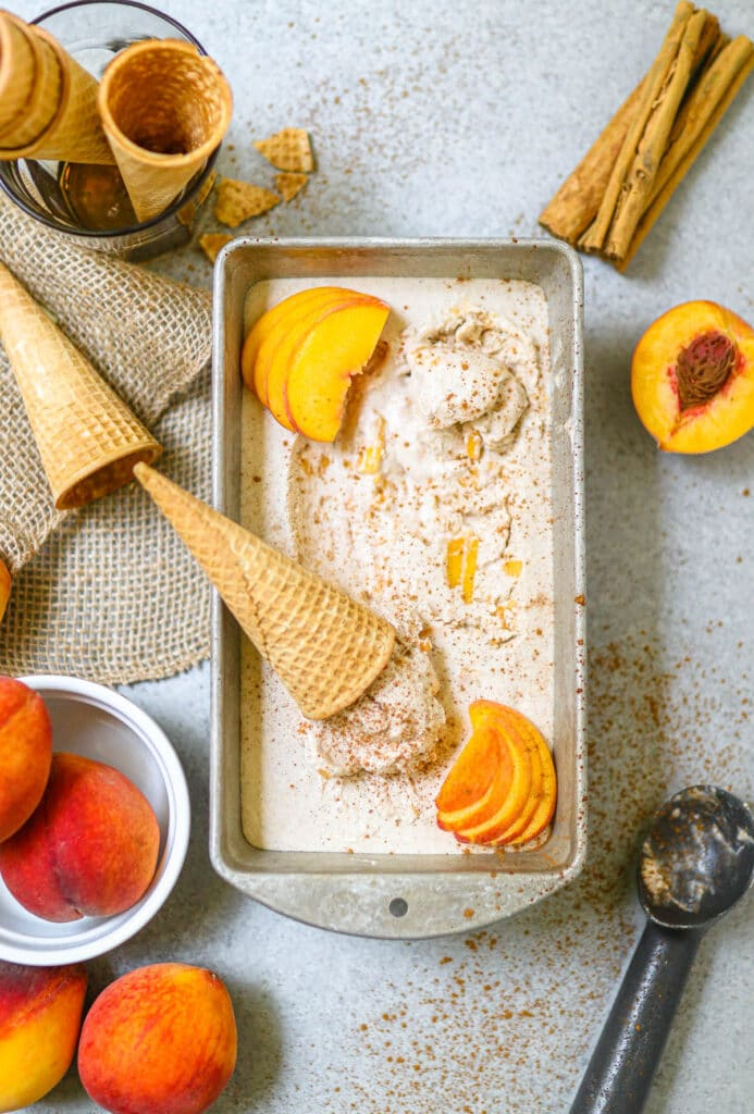 finished photo of peach ice cream in a tub with cones on top, garnishes in the background
