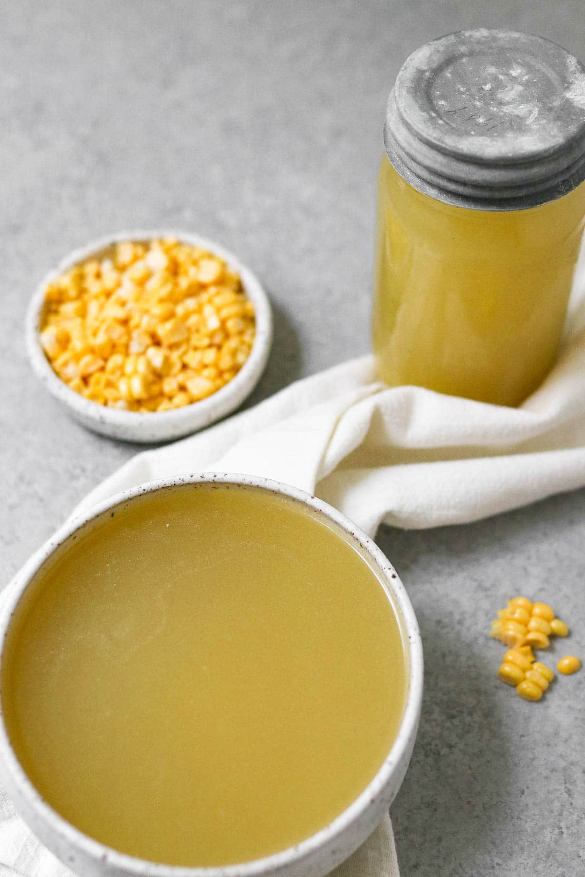 Photo of corn stock in a bowl and in a jar with corn in the background