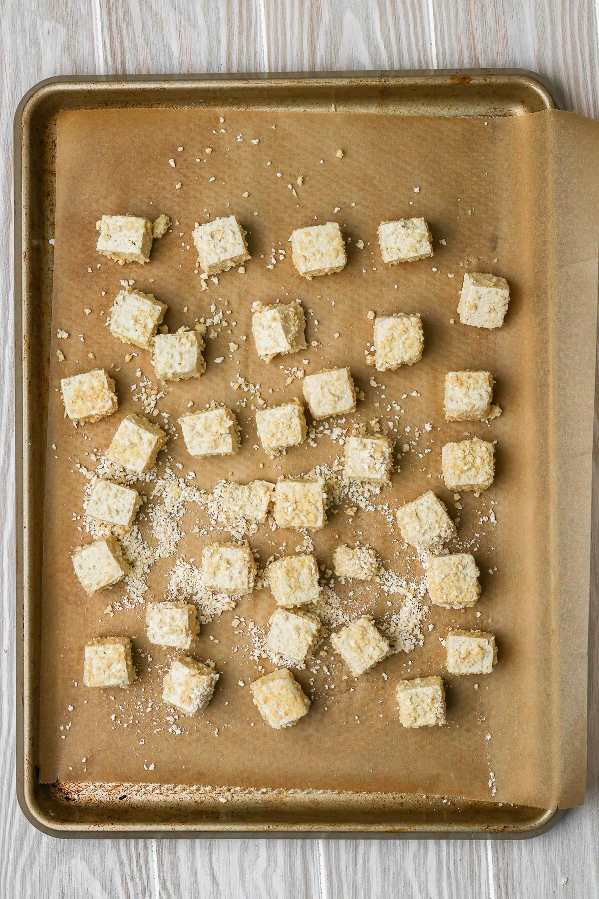 tofu pieces on a baking sheet before baking.