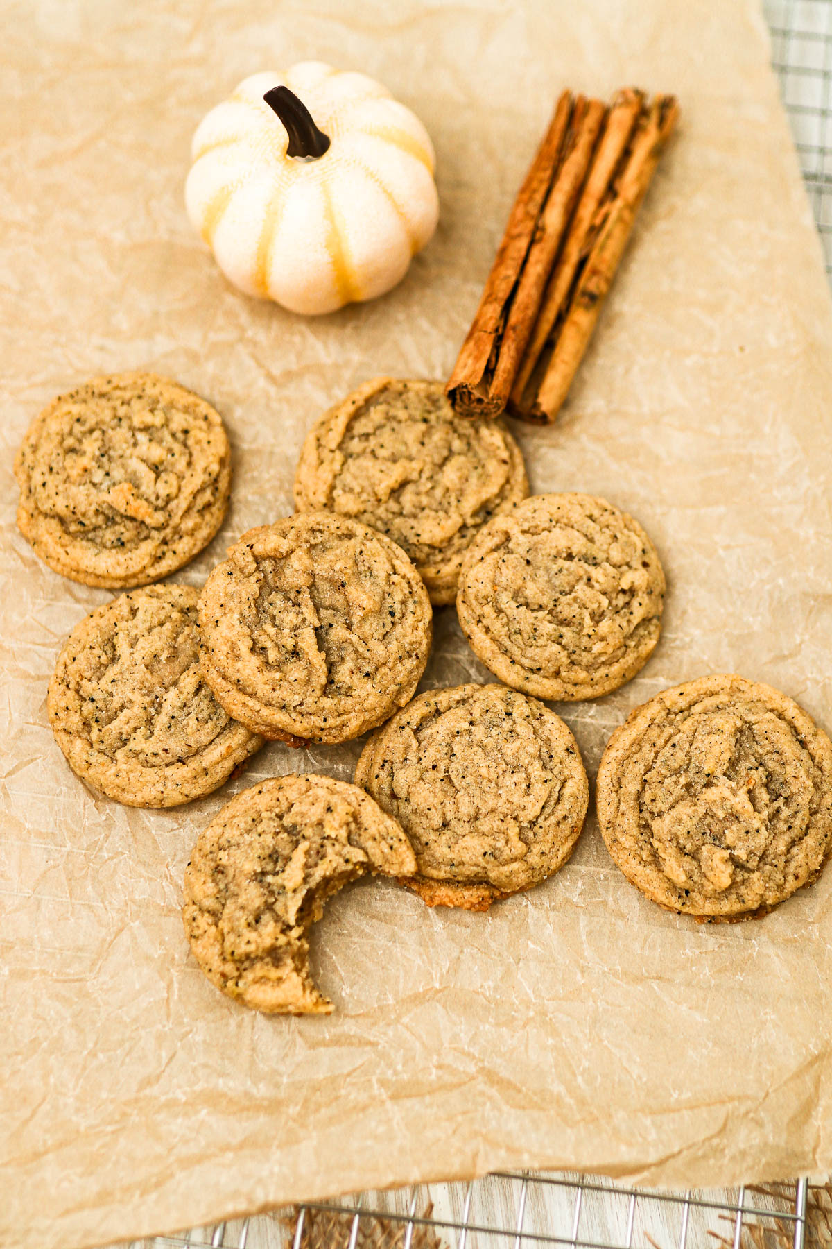 chai cookies on parchment paper with white pumpkin and cinnamon sticks.
