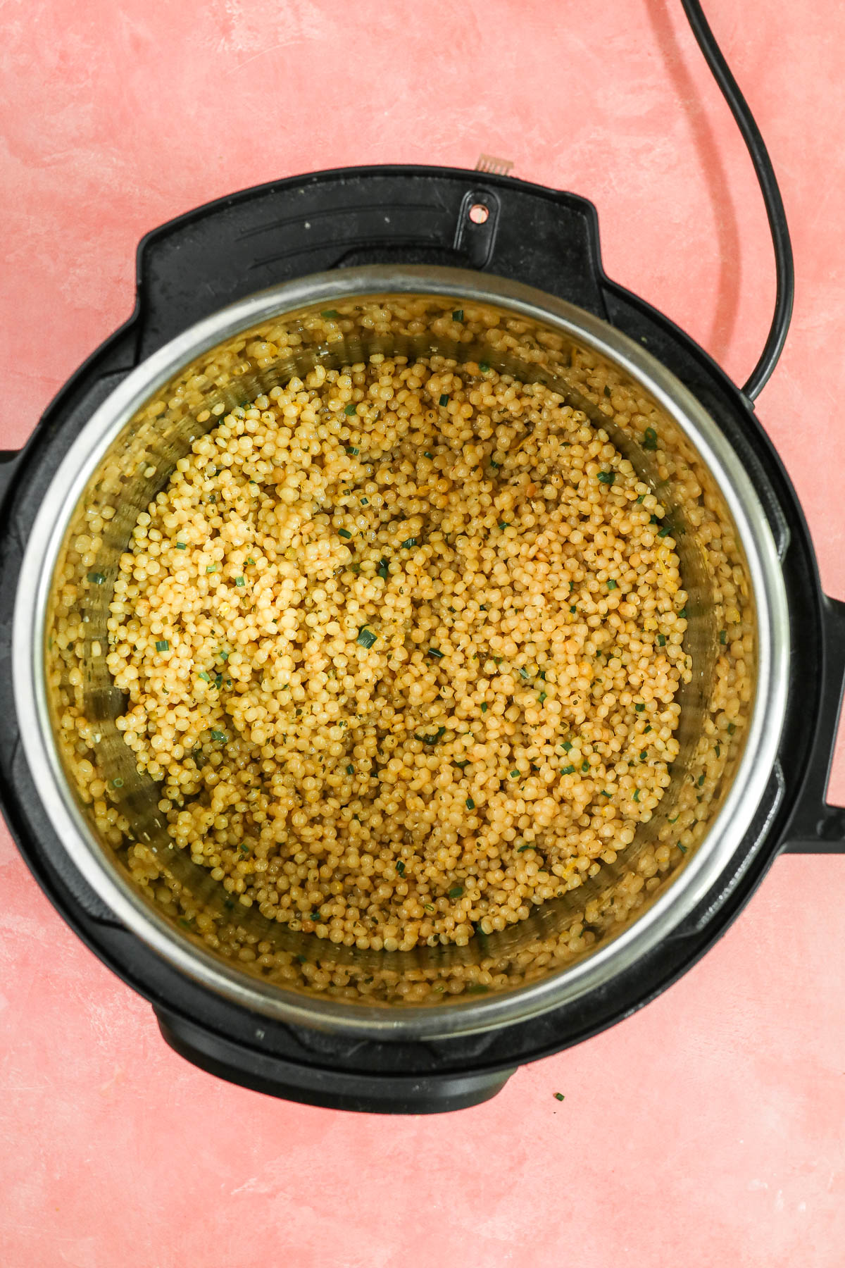 cooked couscous in the instant pot with added ingredients.