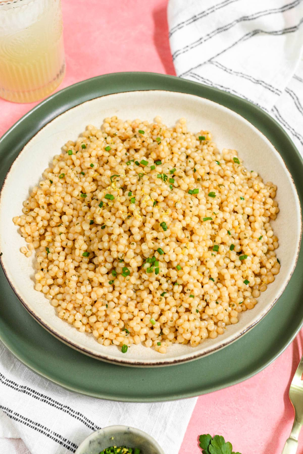couscous on a white plate on a green plate all on a pink table.