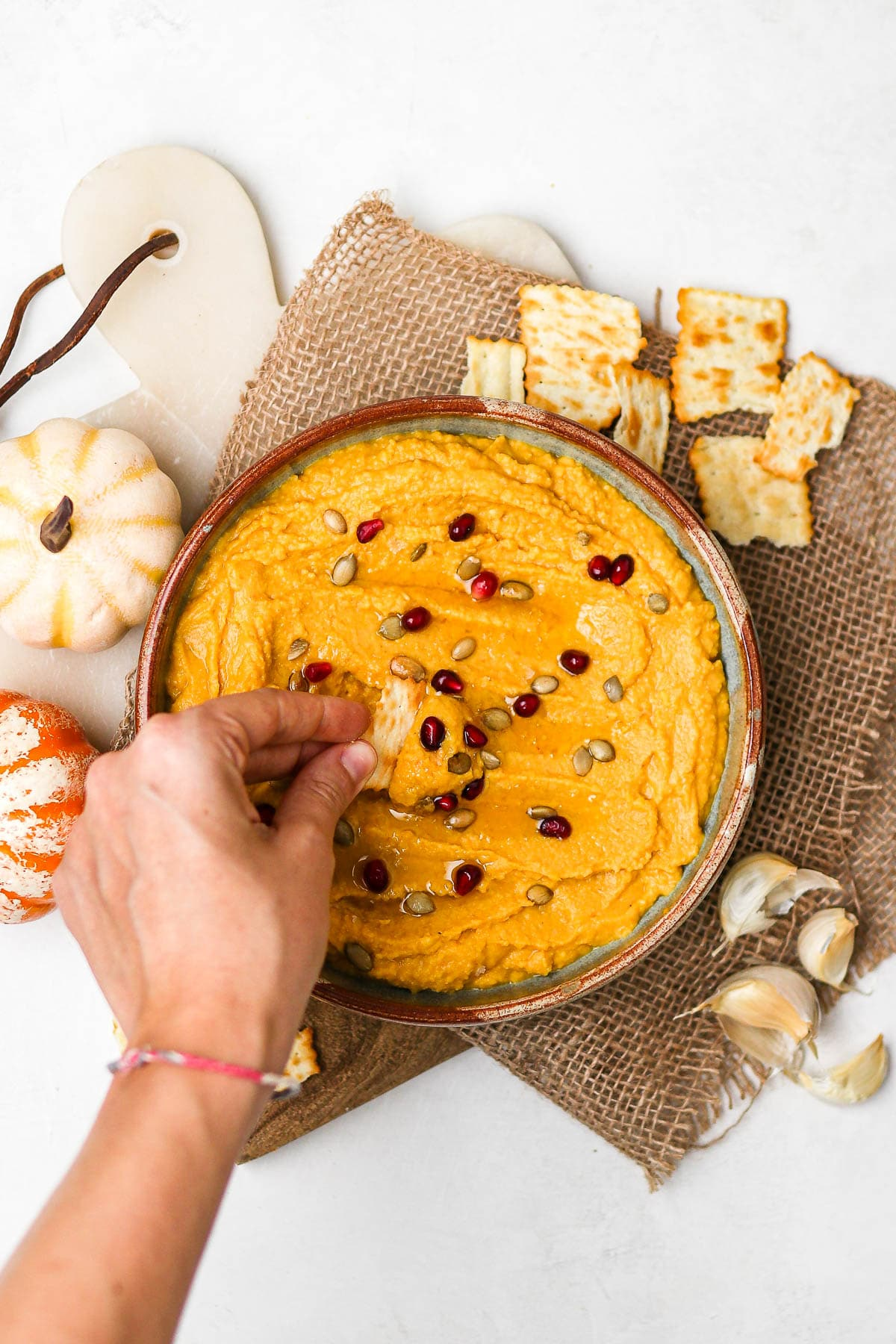 pumpkin hummus in a bowl with hand dipping onto a chip.