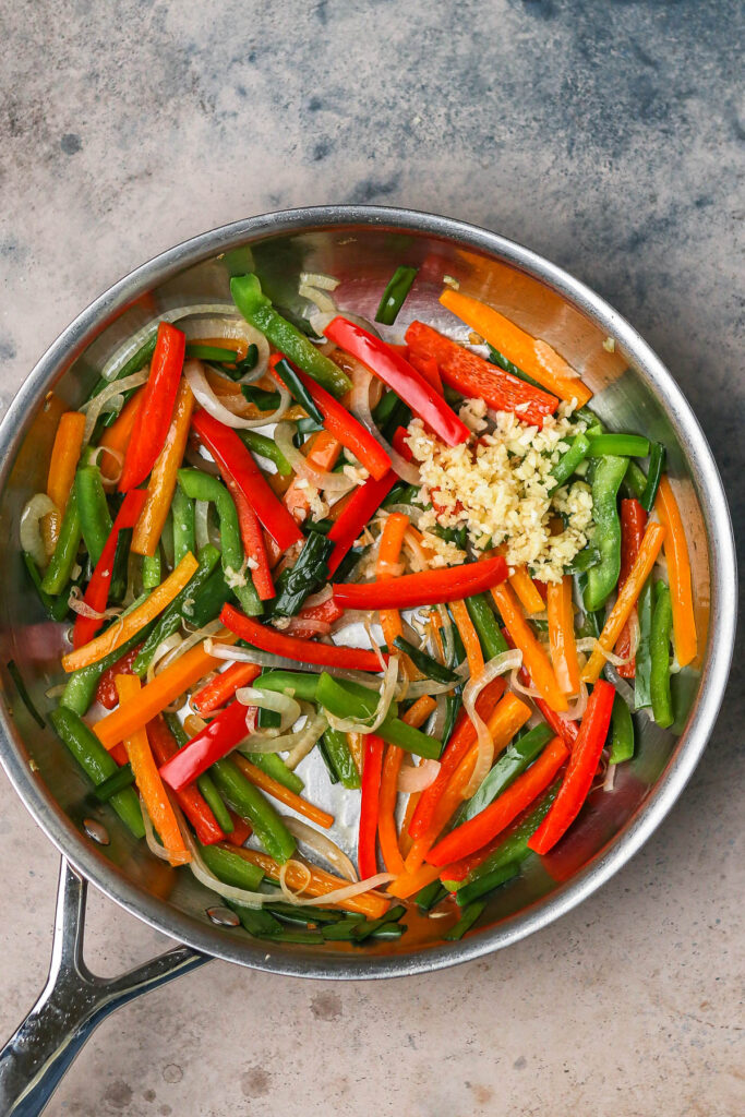 onions, scallions, peppers, and garlic in a silver pan.