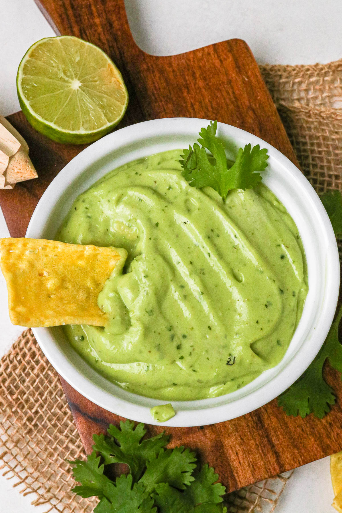 avocado cream sauce in a white bowl with a chip in it.