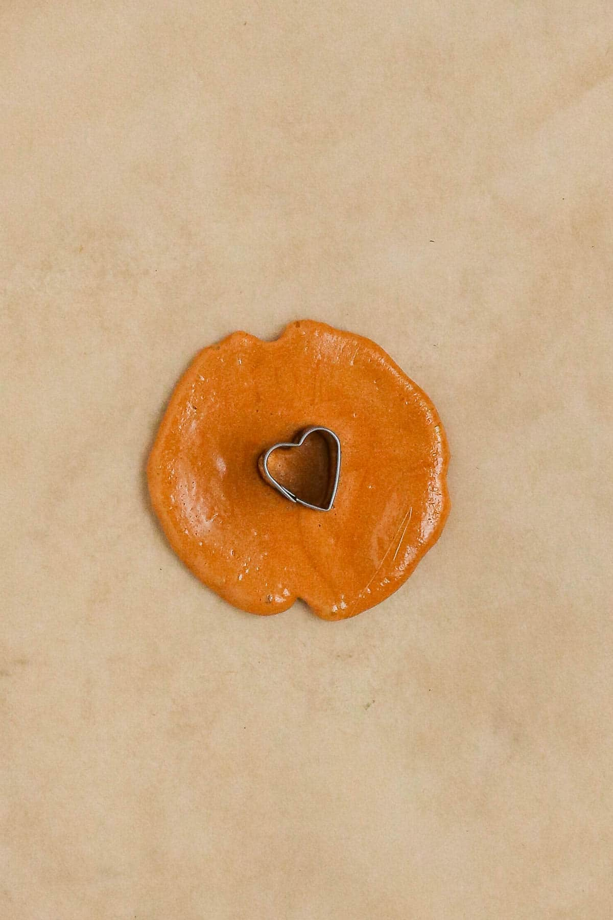 a heart-shaped cookie cutter imprinting the dalgona.