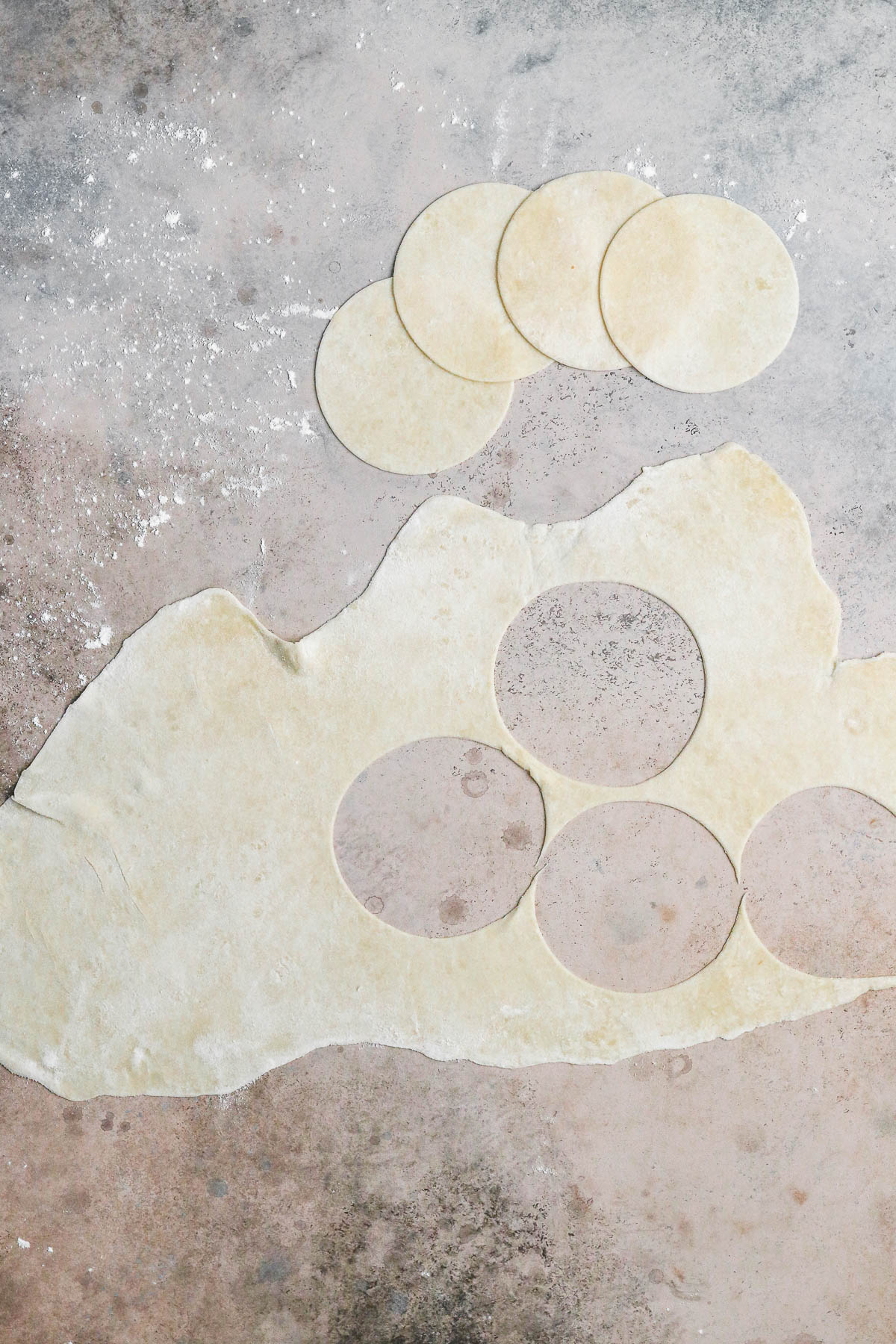rolled out dough with 4 circles cut out of it.